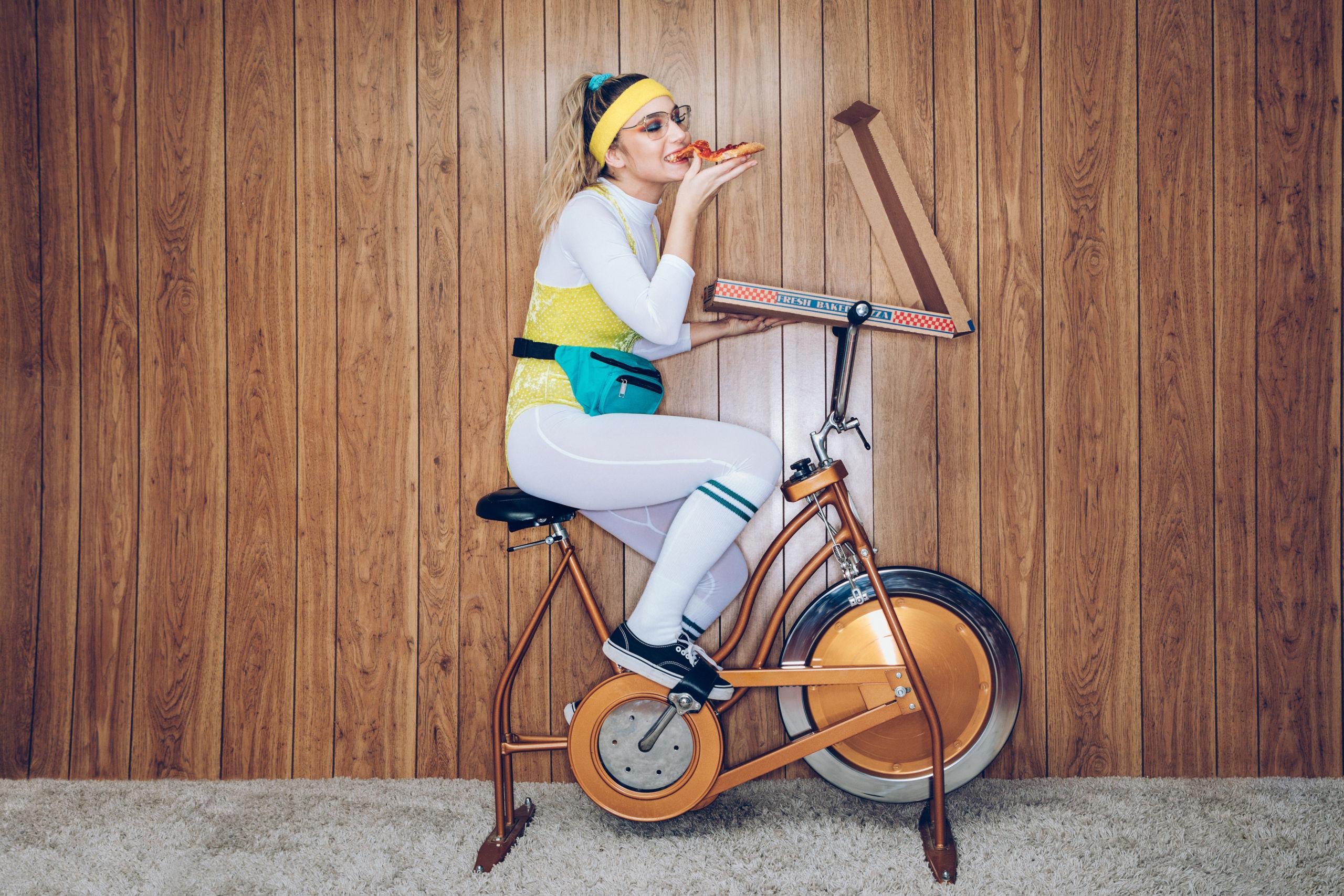 Eine Frau in Trainingskleidung im Stil der 1980er und 1990er Jahre strampelt auf einem stationären Fitnessrad in einem Vintage-Raum mit Zottelteppich und Holzvertäfelung an den Wänden. Sie trägt einen Trikotanzug und eine Gürteltasche und isst aus einem großen Pizzakarton.