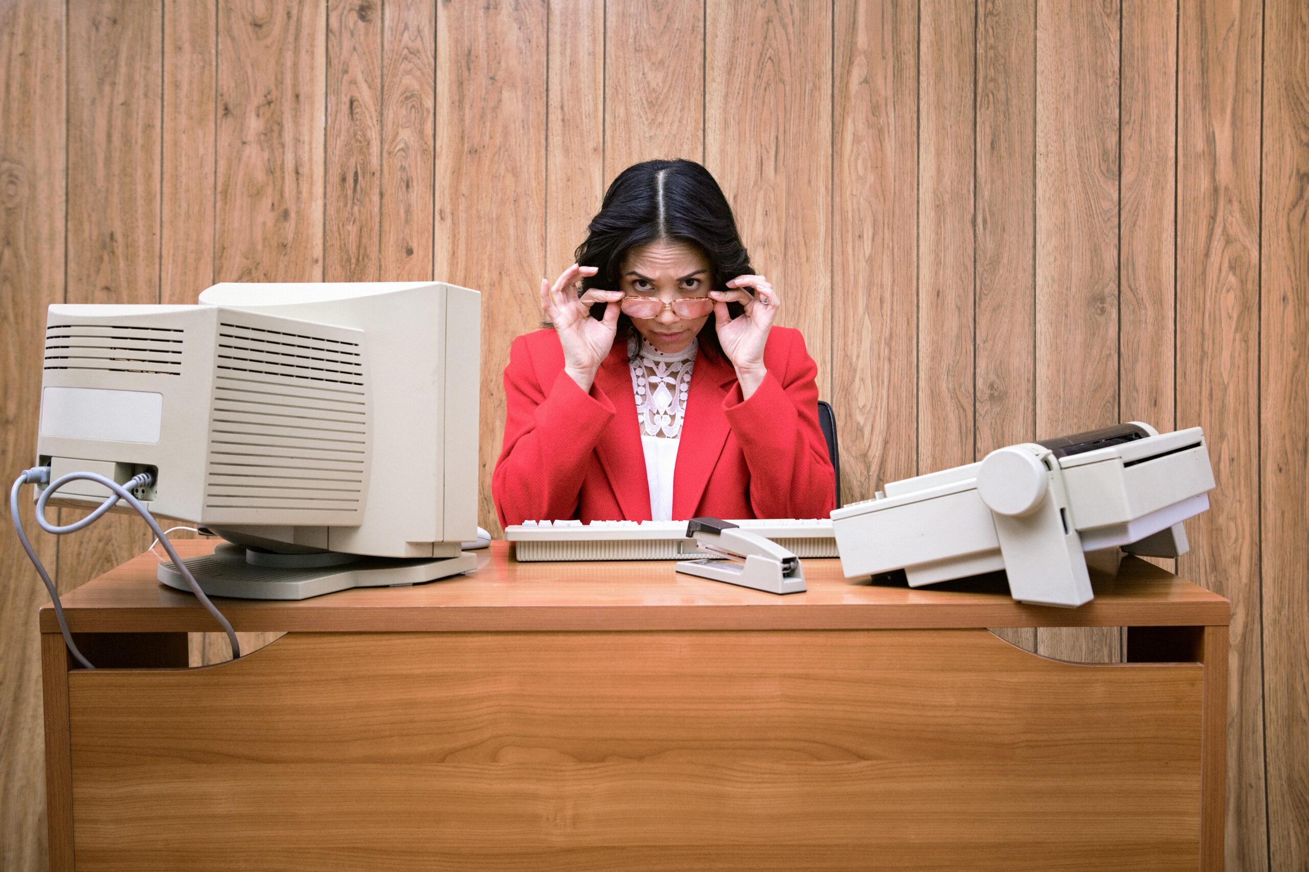 Eine Vintage-Geschäftsfrau im Büro arbeitet an einem alten Computer an ihrem Schreibtisch. 1980er/1990er Jahre Mode-Stil. Holzverkleidung an der Wand im Hintergrund.