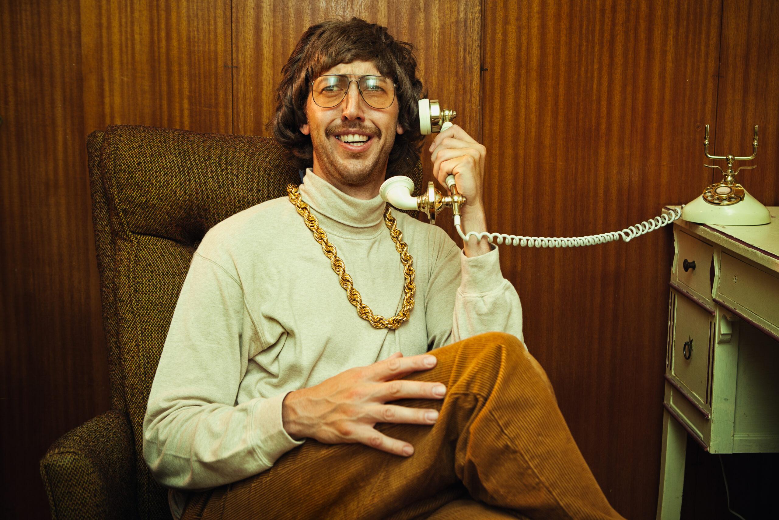 Ein lächelnder, alberner Mann aus den 1970er/1980er Jahren entspannt sich, während er an seinem altmodischen Wählscheibentelefon spricht. Er trägt einen Rollkragenpullover, eine elastische Cordhose mit hoher Taille und seine ausgefallene Goldketten-Halskette. Er trägt eine elegante getönte Brille und einen gepflegten Schnurrbart. Holzpaneelwand im Hintergrund.